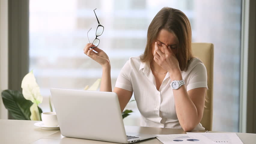 Young businesswoman taking off glasses while working on laptop at office, feeling discomfort and eye strain after long wearing, massaging nose bridge, blurry irritated dry eyes, eyesight problems
