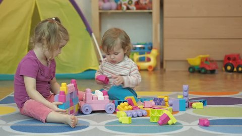 Boy and Girl Build Toy . Children Kid and Baby Play With Blocks. Educational Toys for preschool and kindergarten child. Brother and Sister Playing Plastic Designer Sitting On the Floor.