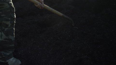 man shoveling dirt into wheelbarrow 2