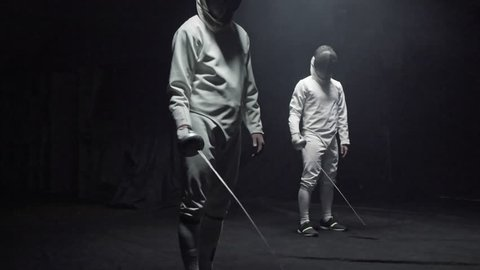 Tracking shot of two fencers in white costumes and protective masks holding foils and looking at camera in dark studio