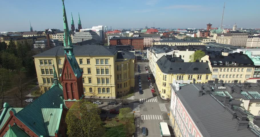 Aerial view drone footage of Helsinki old church, bay area with boats and road traffic near sea terminal and harbour with city skyline and Baltic Sea view in the capital of Finland, northern Europe