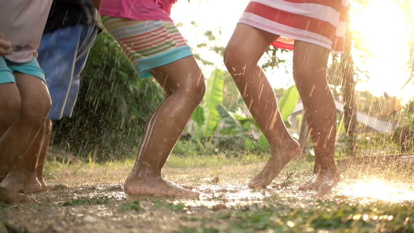 Slow motion of children's feet jumping in the mud in the rainy day.
