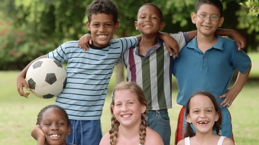 Multiethnic young people pose with soccer ball, portrait of six happy children with football looking at camera and smiling