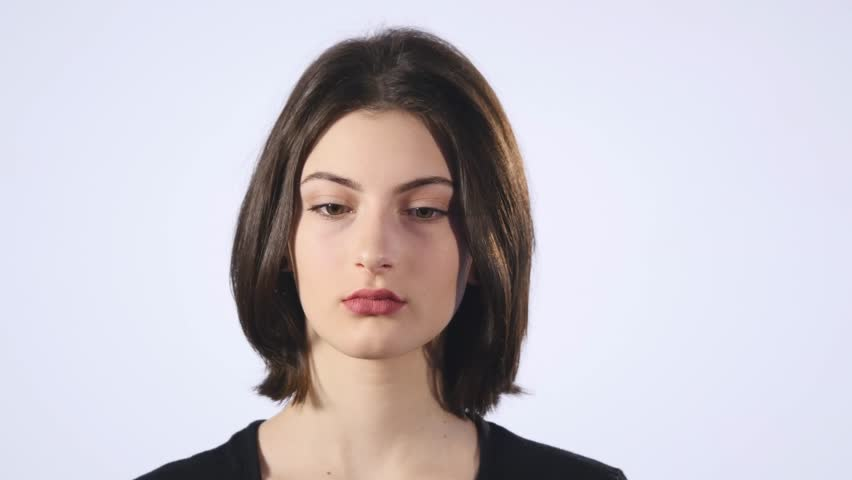 A cute young white woman makes a sad face on a white background.