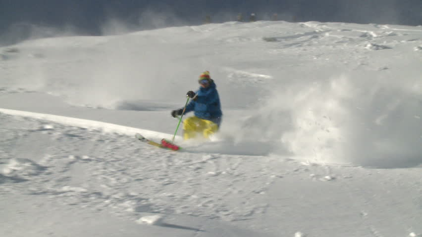 Skiing fast down a steep pitch in cold dry powder. Backlit snow highlights dry, cold, fluffy,  snow quality as skier passes camera. | Shutterstock HD Video #2712014