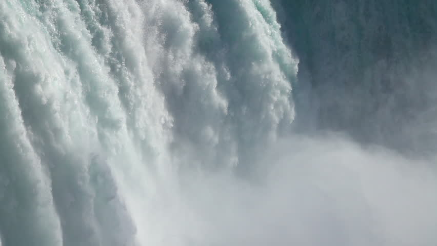 SLOW MOTION, CLOSE UP: Powerful raging whitewater waterfall falling forcefully over a rocky edge. Crystal clear glacier water stream dropping over the cliff. Misty majestic Niagara Falls river rapids