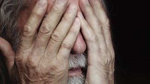 depressed old man with hands on face,close up