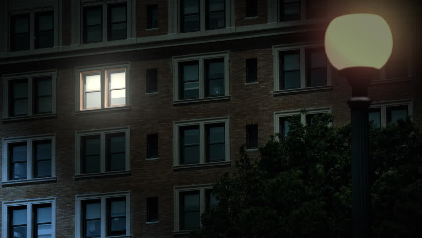 A typical New York style apartment or office building establishing shot at night with the lights from a window turning on. Simulated