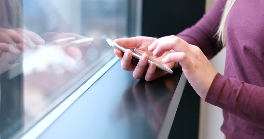 Elegant Woman Using Mobile Phone by window in office building | Shutterstock HD Video #27172252