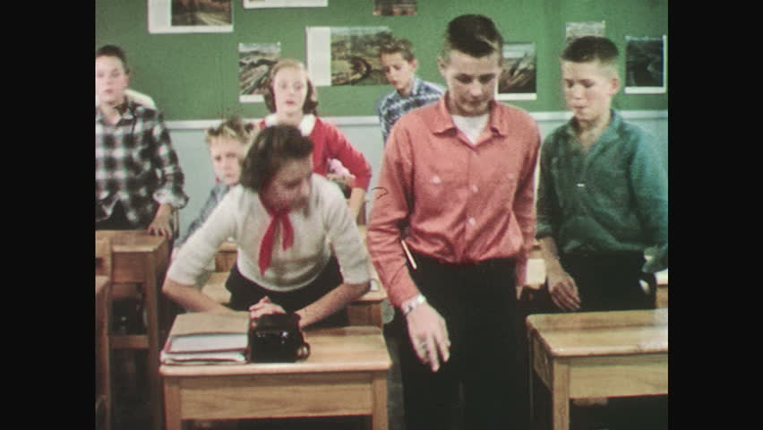 UNITED STATES: 1950s: teacher stands by board. Students pledge allegiance in classroom. Lady swears allegiance. #27173947