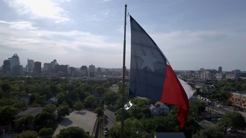 Large Texas flag waving while camera orbits with downtown Austin and the state capital building in the background. Aerial perspective.