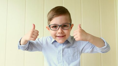 A child with glasses gives a thumbs-up. A kid likes the glasses. Little boy approves.