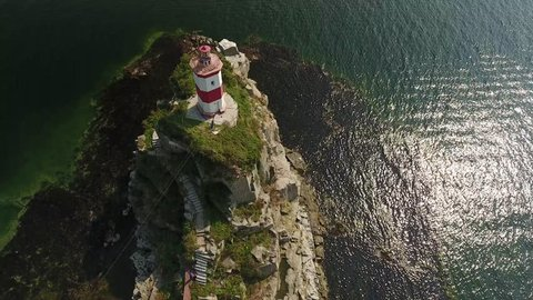 Unique helicopter flight above close Old Lighthouse Basargin Cape. Vladivostok city sightseeing symbol. Best of Russia. Ocean rocks and blue Japan sea water. Aerial drone 4k footage. Summer day