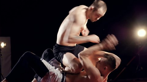 Two fit man, mma fighters fighting on the floor.