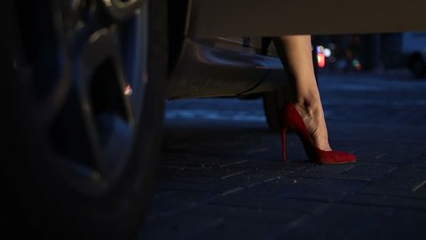 Slender woman's legs in red high heels stepping out of car at night. Perfect female legs in high heel shoes getting out of automobile against cityscape bokeh background. Dolly shot