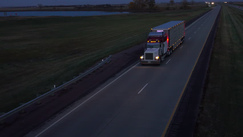 AERIAL, CLOSE UP: Flying above the semi truck carrying freight cattle container for live animal land transportation. Truck in United States hauling livestock box along the country highway at dusk