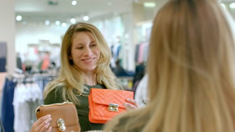Medium shot of stylish woman in green dress looking in mirror in clothing boutique and choosing between two purses