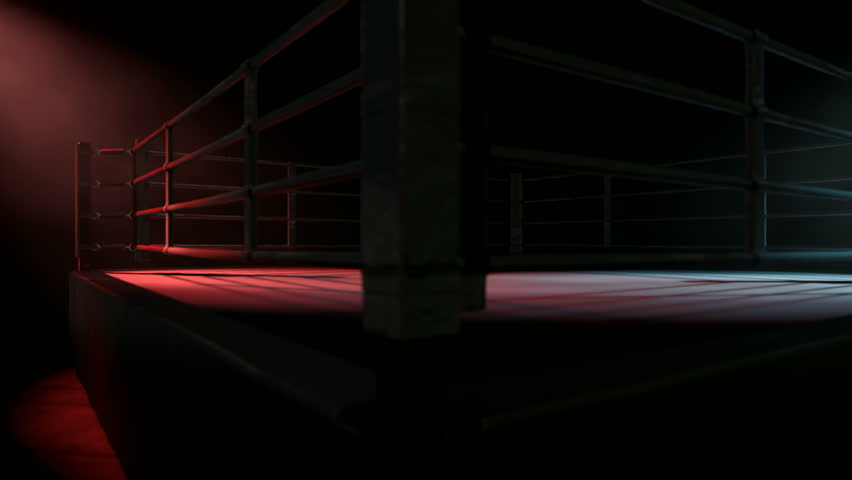 A pan across a empty regular boxing ring surrounded by ropes spotlit in either opposing corner on an isolated dark background