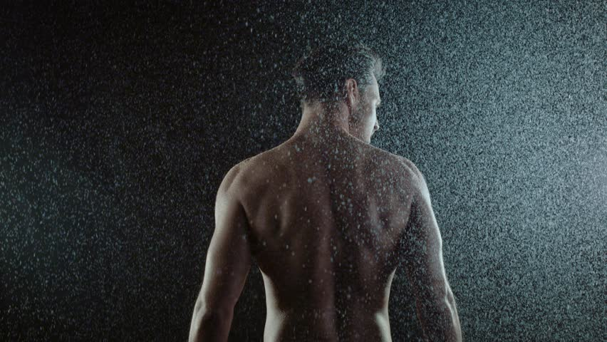 Young man standing in the rain, slow motion 4k Red Epic clip