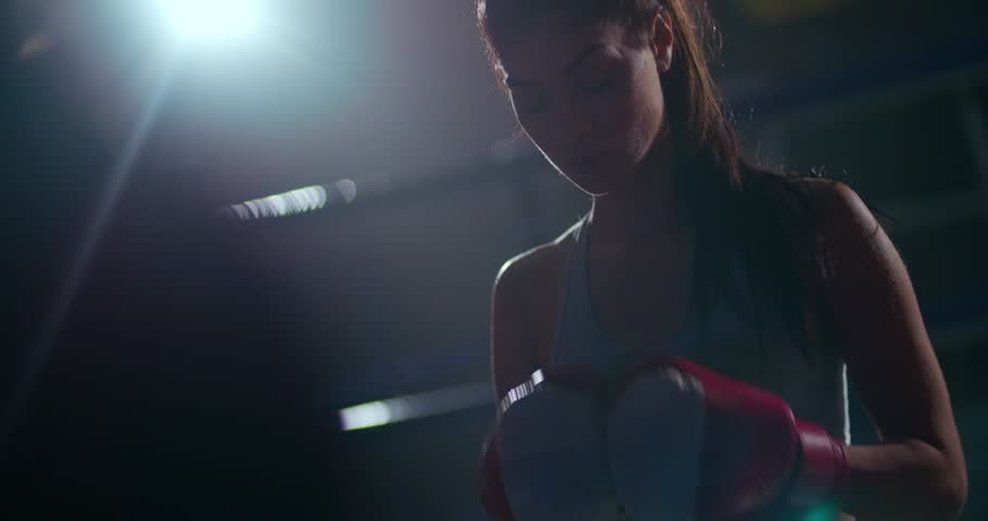 Female athlete with boxing gloves in a boxing ring waiting for the fight to start | Shutterstock HD Video #27279067