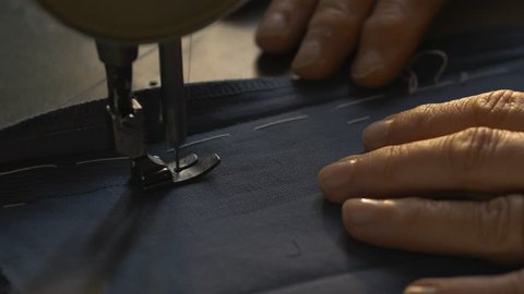 An expert female tailor works on sew machine