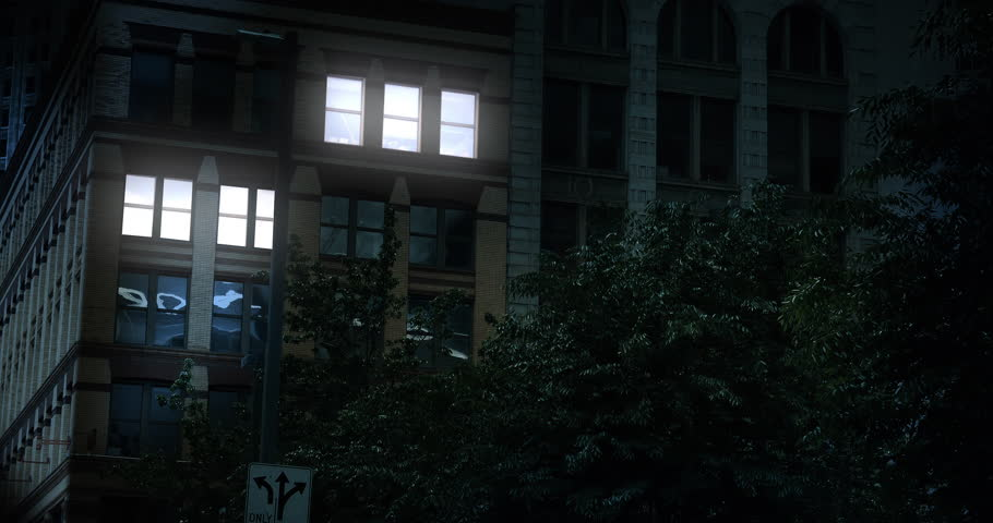 A typical New York style apartment or office building establishing shot at night with the lights from a window turning on and off. Simulated