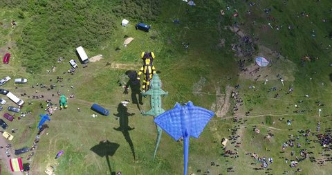 Aerial view of kites with shadow and Tourists on green meadow at Kite Festival