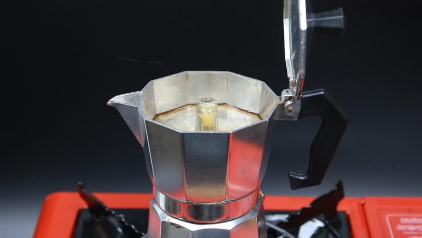 Moka Pot coffee maker on orange stove and a black background. finish with smoke. | Shutterstock HD Video #27305017
