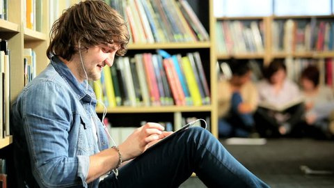 Young male Caucasian classmate using tablet and listening to IT lecture in college hub