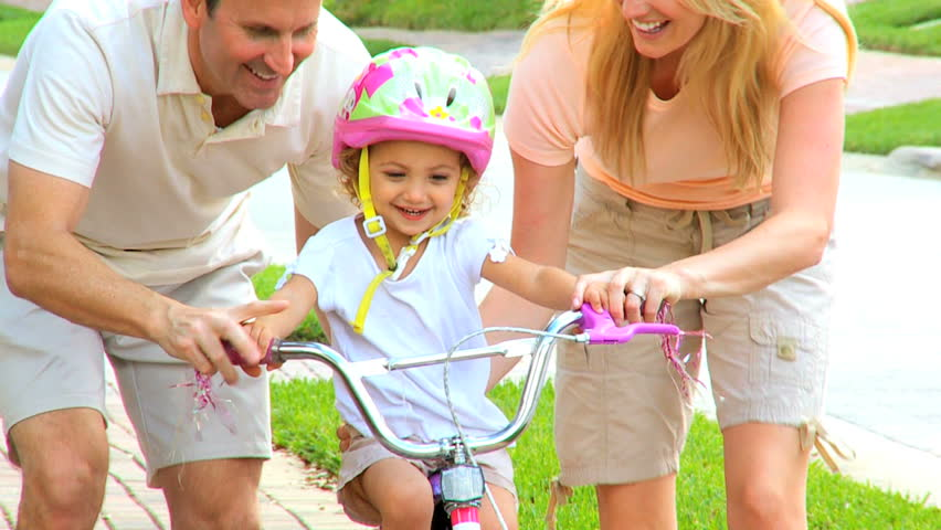Young parents supporting toddler daughter wearing safety helmet on bicycle