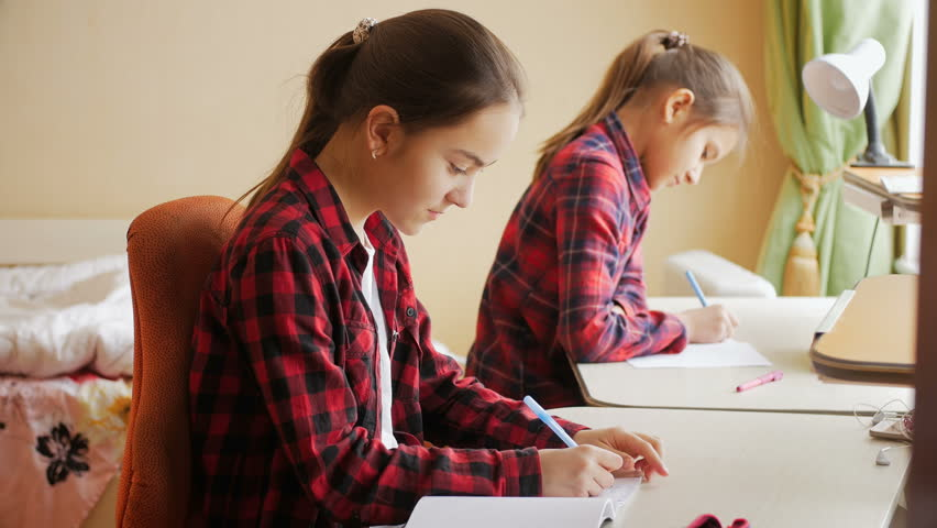 4k footage of two sisters writing in notebooks with pens behind desk at bedroom   Shutterstock HD Video #27329860