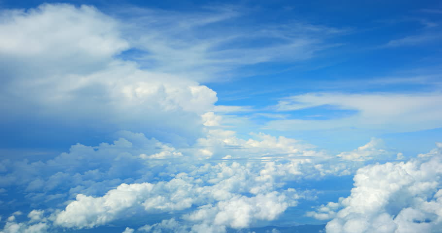 Airborne perspective. flying between two layers of fluffy. white clouds. with a bold. blue sky in the background. 4k footage