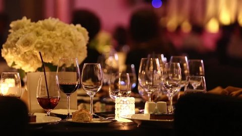 Empty glasses of champagne softdrink, soda and wine on Gala Dinner table, Candle light up with flower bouquet and background of people dancing, blurred silhouettes of guests with moving light around