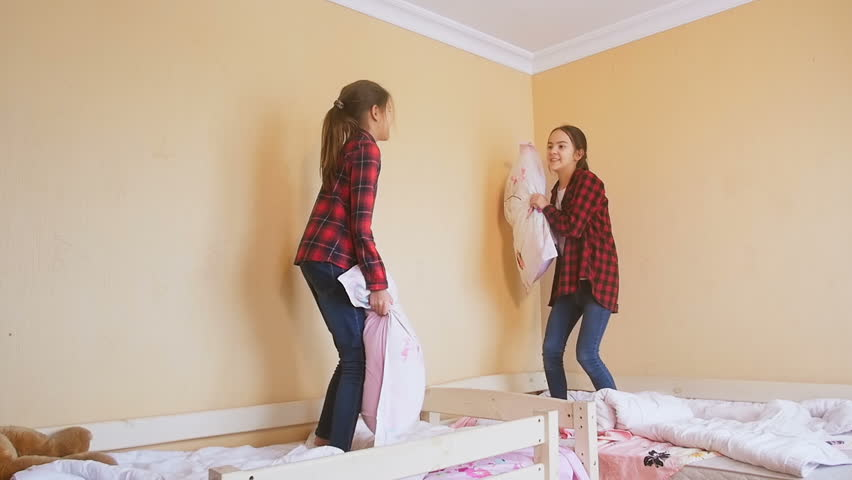Slow motion footage of two teenage sisters fighting with pillows and laughing | Shutterstock HD Video #27348007