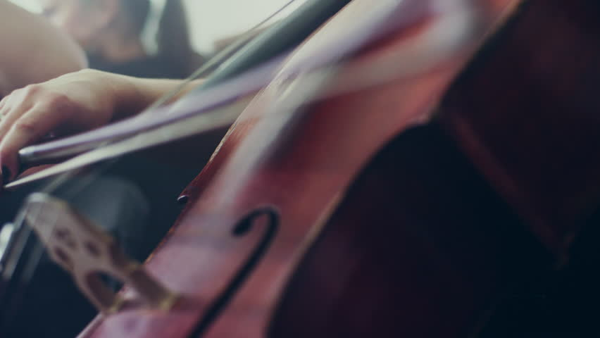 Female cello player playing violoncello. Close up of woman hand playing cello. Cello player playing cello bow. Orchestra musicians instruments