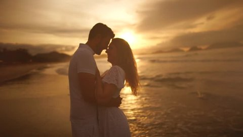 Romantic couple on the beach at a colorful sunrise on background