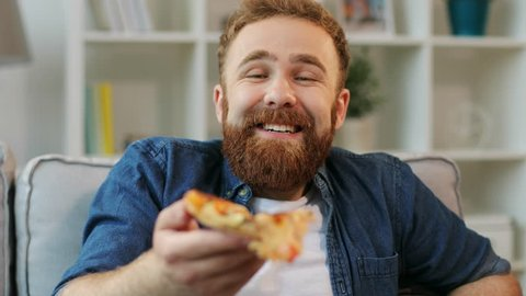 Portrait of young red hair hipster with beard eating pizza, watching favorite comedy on tv while relaxing at sofa in the living room. Close up.