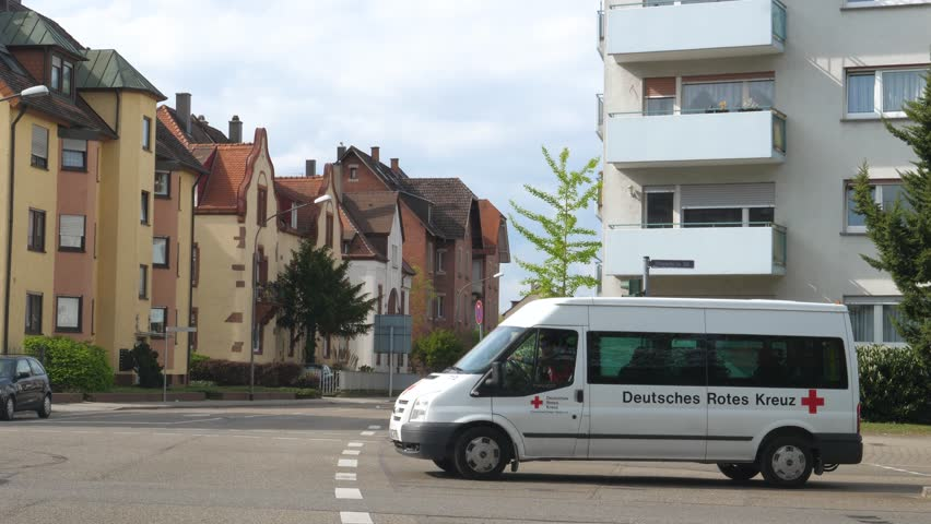 RASTATT, GERMANY - CIRCA 2017: Ambulance doctor and Ford Transit Ambulance Van driving in a row in German city of Rastatt - Deutsches Rotes Kreuz