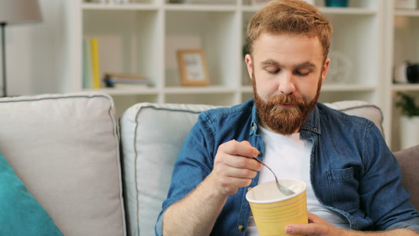 Portrait of young man who eating ice cream while relaxing on sofa in the living room at home.