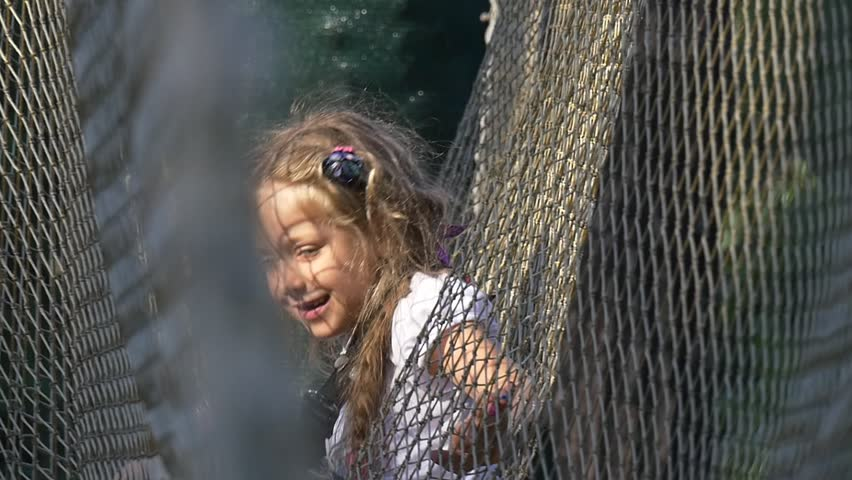A Small Fair-Haired Schoolgirl Plays in a Park of Adventures. a Long Fishing Grid Hangs Between Two Trees. the Girl Has Got Into Her and Sits There. This Video Was Recorded on Camera With Help of a | Shutterstock HD Video #27445267