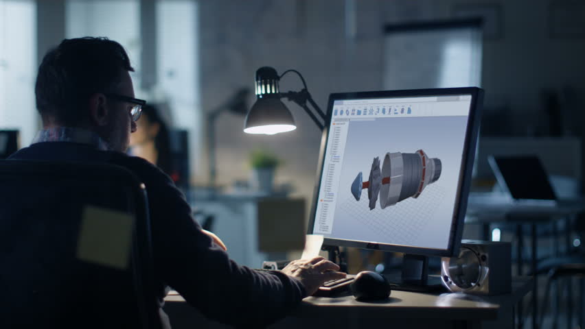 Late at Night in the Office. Design Engineer Works on His Personal Computer. On His Display We See Blueprints. Office Looks Modern. In the Background People Working.