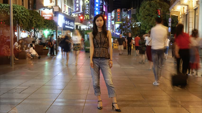 SHANGHAI JUNE 2017: Woman stands at Shanghai Nanjing East road in night timelapse. Evening time-lapse of still Asian girl standing on busy pedestrian street in with people and trams moving past.
