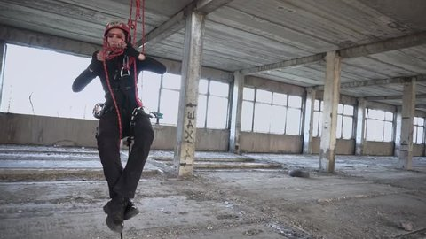 Industrial climber untying knot on rope closeup