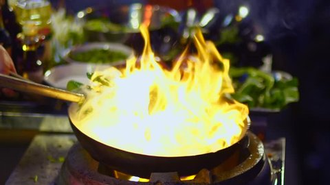 Street-side wok fire in Shanghai slow motion. Slowmo cook fires up hot oil with vegetables outside on the road at night in downtown Shouning rd food street in China.