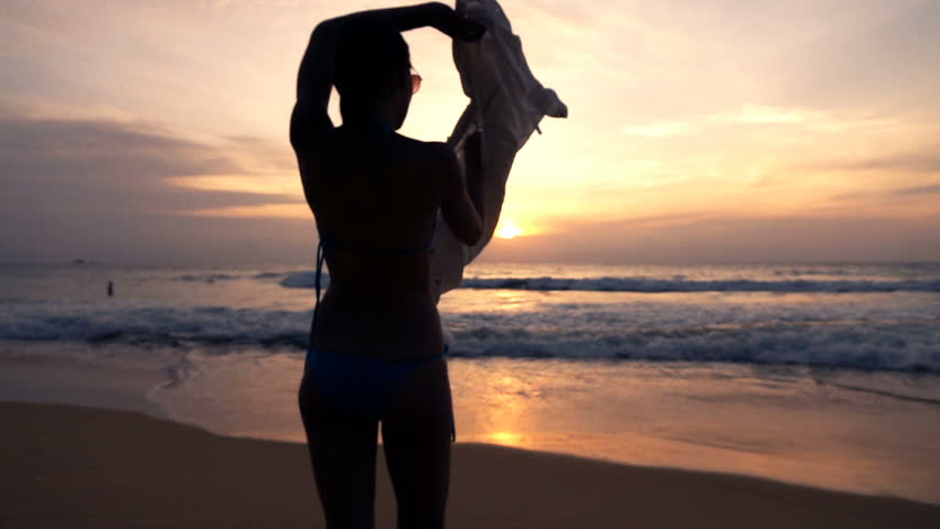 woman putting on shirt standing on beach during sunset super slow motion 240fps hd