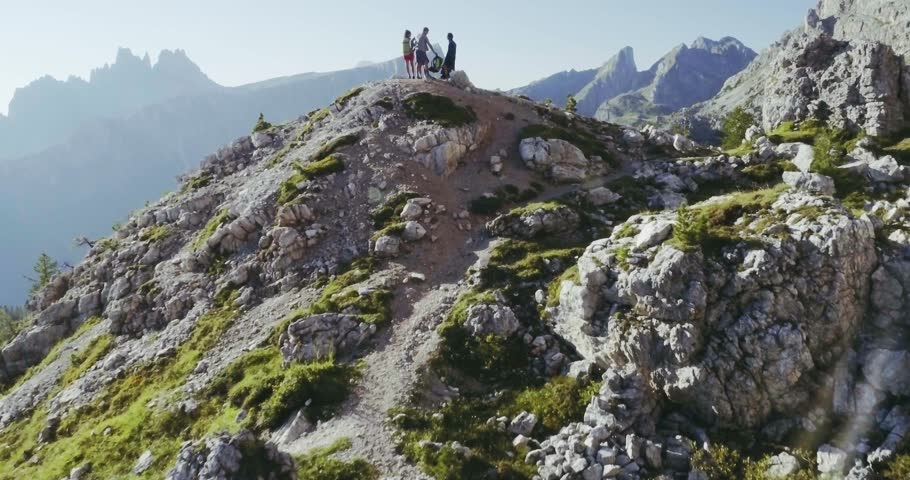 Aerial flight above people hiking along trail path in sunny day. Group of friends summer adventure journey in mountain nature outdoors. Travel exploring Alps, Dolomites, Italy. 4k drone forward video | Shutterstock HD Video #27553507