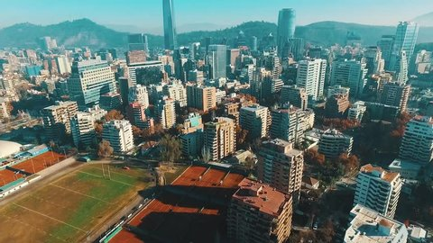 Aerial footage of Santiago de Chile, revealing the financial district, some tennis court and The Andes Mountains from the air.