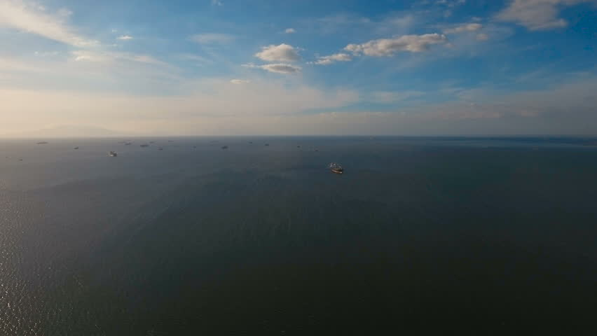 Aerial view Cargo ships in the Bay of Manila. Large container ship in the sea. Flying over the water surface of the sea with ships, blue sky and clouds. 4K video. Aerial footage. Philippines, Manila.   Shutterstock HD Video #27562267