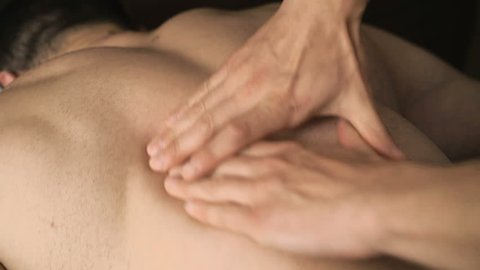 The masseur doing sports health massage of back for sportsman