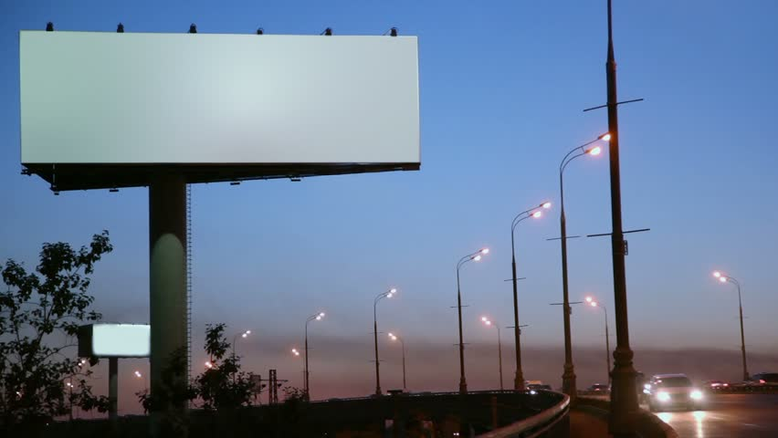 Empty advertising billboard on sidelines of road with traffic at evening #2761067
